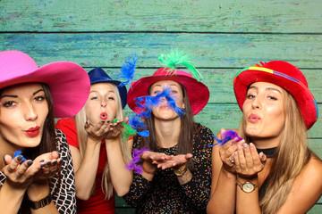 Frauen mit Hüte pusten bunte Federn aus den Händen - Spaß mit der Fotobox