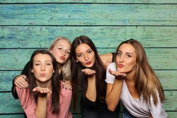 4 Mädchen machen Pusteküsse in eine Fotobox - 4 Freundinnen mit Photobooth