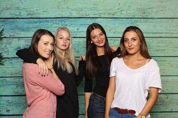 4 Freundinnen stehen vor einer Fotobox - 4 Mädchen lächeln in eine Fotobox