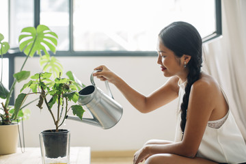 Young woman at home watering plant