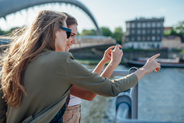 Two girls taking picture of the cityscape. River in the backgrou