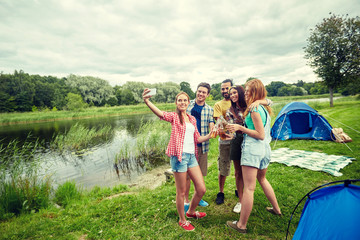 happy friends taking selfie by smartphone at camp