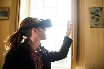 Close-up of hipster gesturing while using virtual reality simula