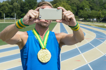 Gold medal athlete making faces at his mobile phone taking a selfie at running track