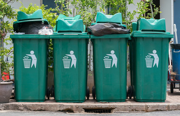 Row of green and clean rubbish bins on the street.