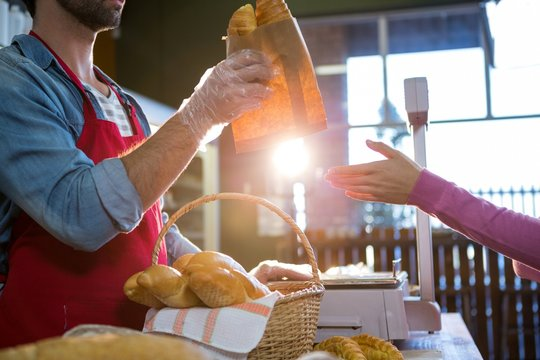 Staff giving packet bread to customer