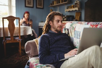 Hipster man using laptop while woman sitting at home