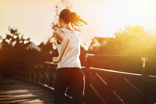 Beautiful jogger crossing bridge