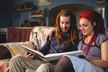 Couple looking photo album on couch
