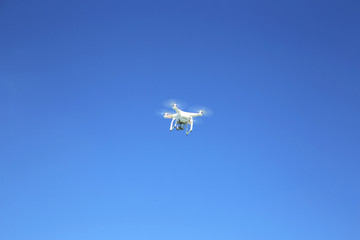 White drone  flying with camera record liens against blue sky