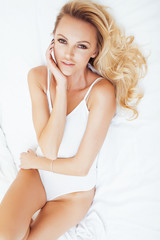 young pretty blond woman in bed covered white sheets smiling cheerful sexy look close up, happy morning concept