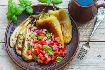 Baked vegetables. Bell peppers and eggplant cooked on the fire. Served with a salad of tomatoes, red onion and Basil. Rustic style