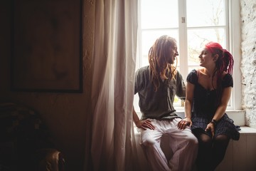 Couple sitting against window at home