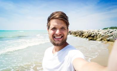 Hipster man on beach, smiling, taking selfie, sunny summer