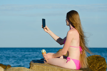 Girl in swimsuit with ice cream in hand on rocky beach makes selfie phone against the sea