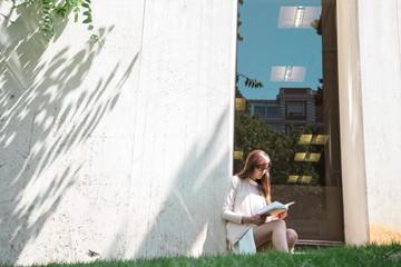 Businesswoman reading in garden at window