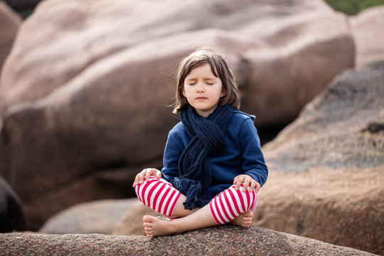 meditating child with eyes closed sitting, relaxing for yoga exercise