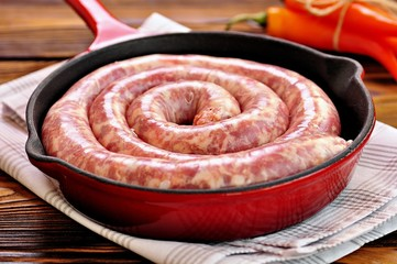 Raw pork sausage in a cast iron frying pan on a wooden background.