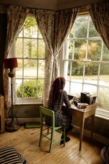 Woman using tablet computer by window