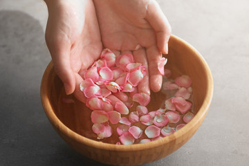 Hands in wooden bowl with petals and water