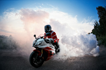 biker staying on bike  road with smoke of the tire, burn out in the moto show.  the Sunset