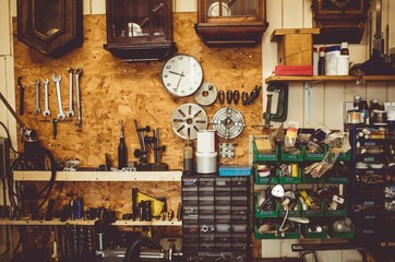 Horologists workshop with clock repairing tools, equipment and clocks on the wall