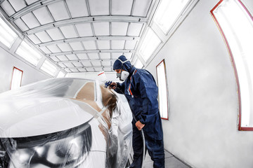 worker painting a white car in special garage, wearing costume and protective gear