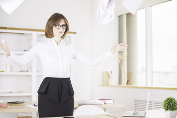 Angry woman throwing papers in office