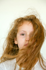 little girl with hair blowing in face