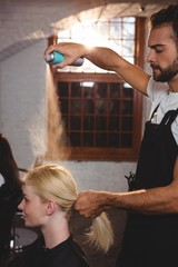 Male hairdresser styling customers hair with hair spray
