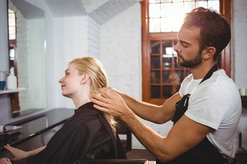 Handsome hair stylist styling woman hair