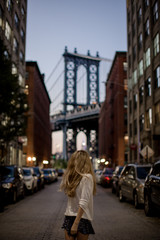 Lady standing on old street, looking  at manhattan bridge