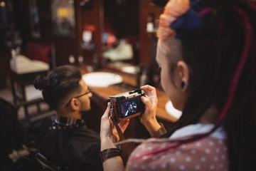 Female barber taking photo of client from digital camera