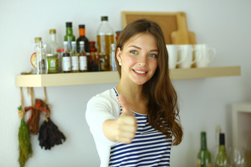 Young woman standing near desk in the kitchen and showing ok