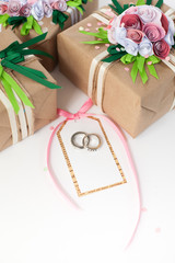 Gifts decorated paper pink flowers. Wedding rings in white gold.
