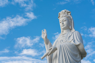 The statue of Guanyin with blue sky and copy space. - Chinese goddess statue (a public temple , can take picture )