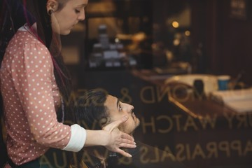 Man receiving a face massage from a female barber