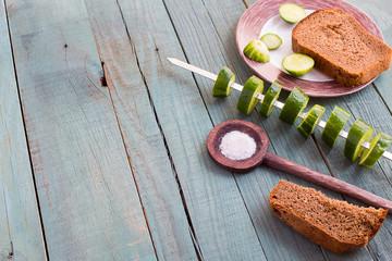 Slices of cucumber strung on a skewer. Vegetarian barbecue cucumber. Black bread and salt. Blue background.