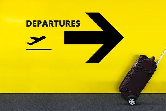 Airport Sign With Departures Airplane Icon on the Yellow Wall. Passenger Rolling the Luggage in Motion