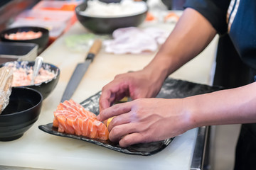 male cooks preparing sushi in restaurant kitchen