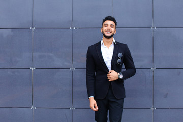 Arabic guy in business center stands smiling walking slow