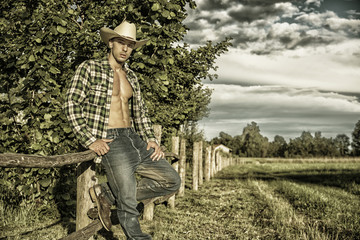 Portrait of sexy farmer or cowboy in hat looking at camera while leaning on wooden fence in countryside