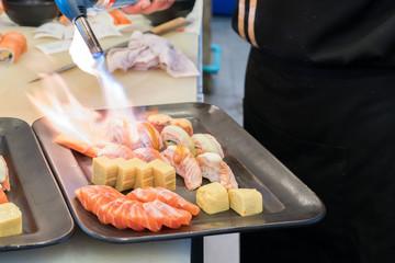 Torch burner over sushi rolls. Man's hand holding torch burner. Chef prepares uramaki sushi.