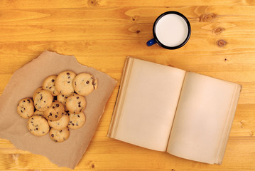 Homemade chocolate chip cookies, milk cup and book