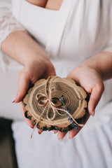 Woman holds wedding rings on wooden holder