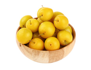 Fresh yellow plums in wooden bowl over white
