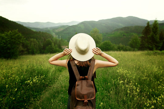 woman traveler with backpack holding hat and looking at amazing