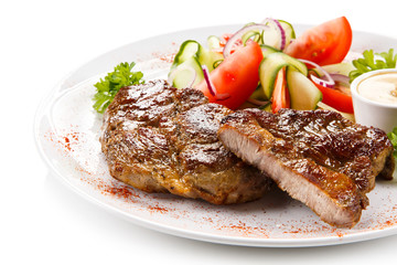 Grilled steaks on white background