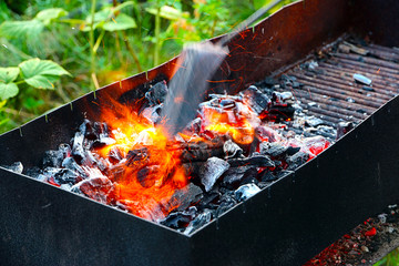 bright hot flame and glowing pieces of charcoal in the brazier