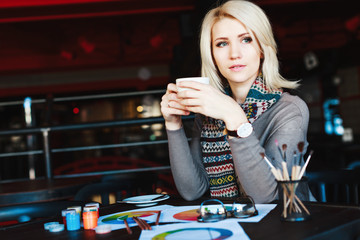 Blonde girl sitting in cafe with cup of tea